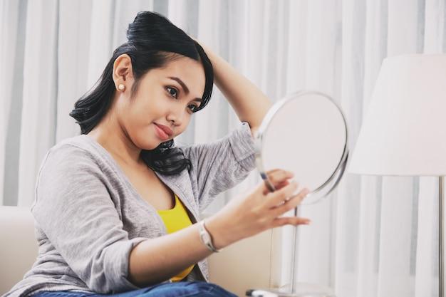 Philippinische frau, die spiegel betrachtet und frisur macht