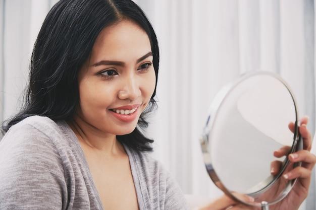Philippinische frau, die spiegel betrachtet