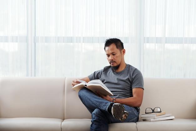 Philippinischer mann, der auf couch mit fuß auf knie und lesebuch sitzt