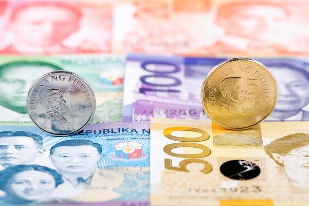 Philippinischer peso prägt auf dem hintergrund von banknoten