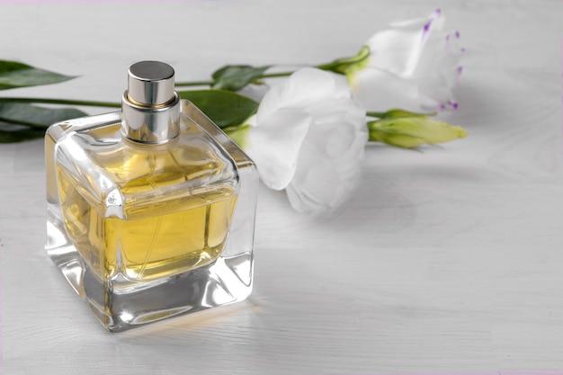 Phiole mit parfüm und schönen weißen blüten von eustoma auf weißem holzhintergrund