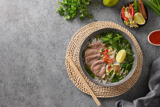 Pho bo suppe mit rindfleisch in grauer schüssel auf grauem hintergrund vietnamesische küche