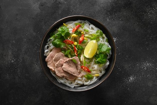 Pho bo suppe mit rindfleisch in schüssel auf schwarzem hintergrund vietnamesische küche