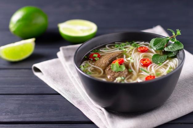 Pho bo - vietnamesische frische reisnudelsuppe mit rindfleisch, kräutern, limette und chili. vietnamesisches nationalgericht.