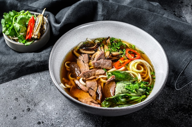 Pho bo vietnamesische frische reisnudelsuppe mit rindfleisch, kräutern und chili. schwarzer hintergrund. draufsicht