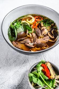 Pho bo vietnamesische frische reisnudelsuppe mit rindfleisch, kräutern und chili. weißer hintergrund. draufsicht
