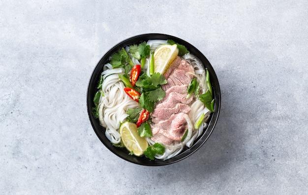 Pho bo vietnamesische suppe mit rindfleisch- und reisnudeln auf einem konkreten hintergrund, draufsicht