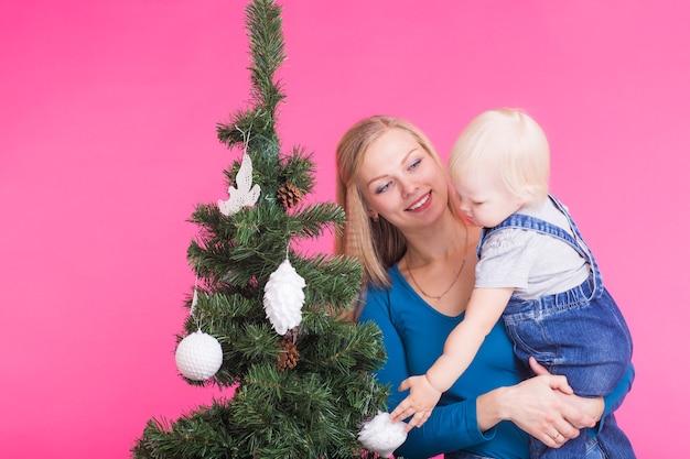 Pholidays, familie und weihnachtskonzept - junge frau mit ihrem baby nahe weihnachtsbaum auf rosa wand.