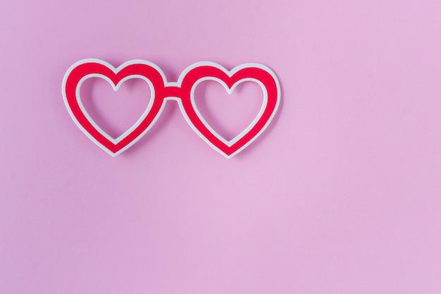 Photo booth requisiten gläser auf rosa hintergrund. herzförmige rote brille. valentinstag, geburtstag oder party festgelegt. ansicht von oben. flach liegen. kopieren sie platz.