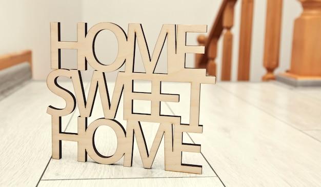 Phrase home, süßes zuhause aus holz auf einem neuen haus