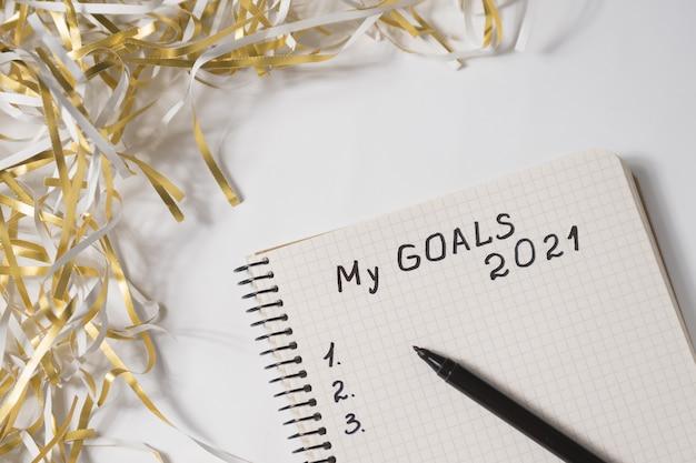 Phrase my goals 2021 in einem notizbuch, stift. lametta auf weißem hintergrund. nahansicht.