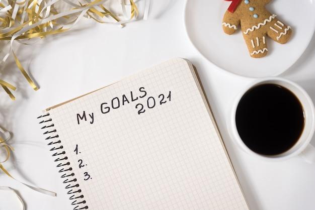 Phrase my goals 2021 in einem notizbuch. tasse kaffee, lebkuchenmann und lametta. nahansicht.