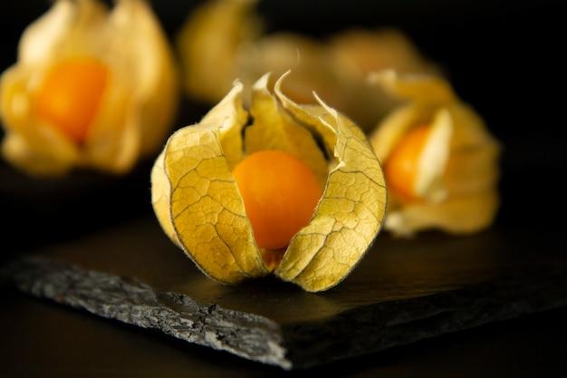 Physalis blüht, die früchte, die auf einem schwarzen hintergrund lokalisiert werden.
