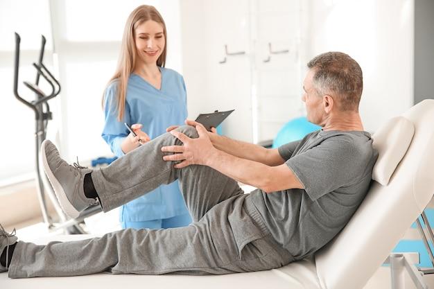Physiotherapeut arbeitet mit reifen patienten im rehabilitationszentrum