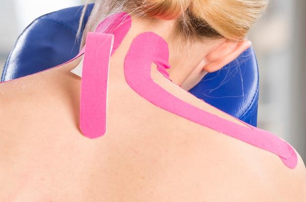 Physiotherapeut, chiropraktiker, der auf rosa kinesio band auf frauenpatienten sich setzt. zervikal