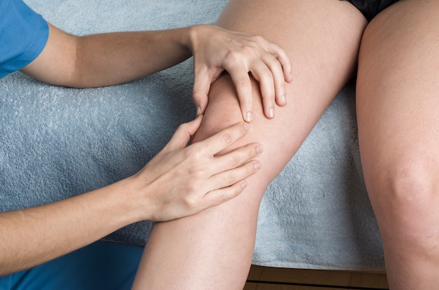 Physiotherapeut, chiropraktiker, der eine patellar-mobilisierung durchführt, knieschmerzen