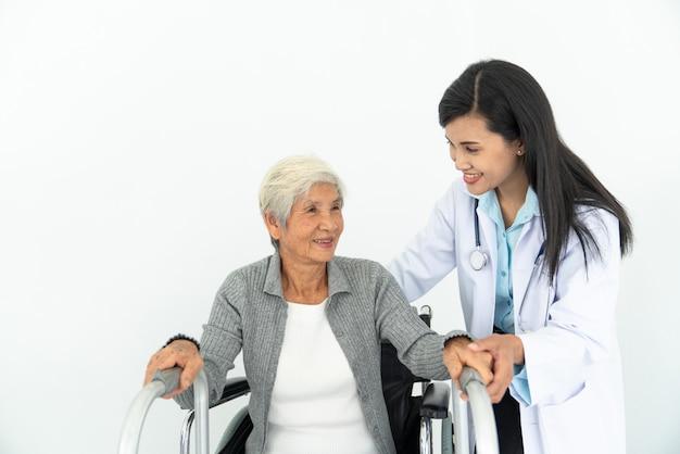 Physiotherapeut, der älteren patienten betrachtet, der im rollstuhl sitzt, arzt und patient im rollstuhl