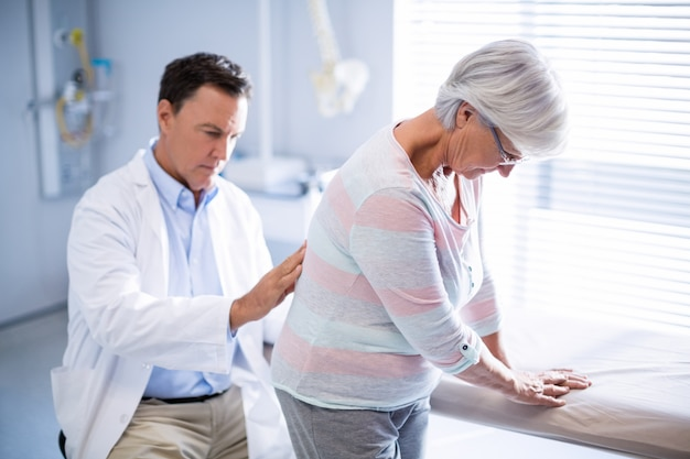 Physiotherapeut, der älteren patienten rückenmassage gibt