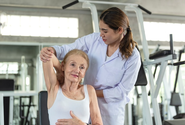 Physiotherapeut, der alter älterer frau in der körperlichen mitte hilft. älteres gesundheitslebensstilkonzept.