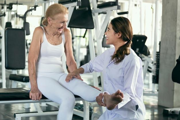 Physiotherapeut, der alter älterer frau in der körperlichen mitte hilft. lebensstilkonzept für ältere menschen.