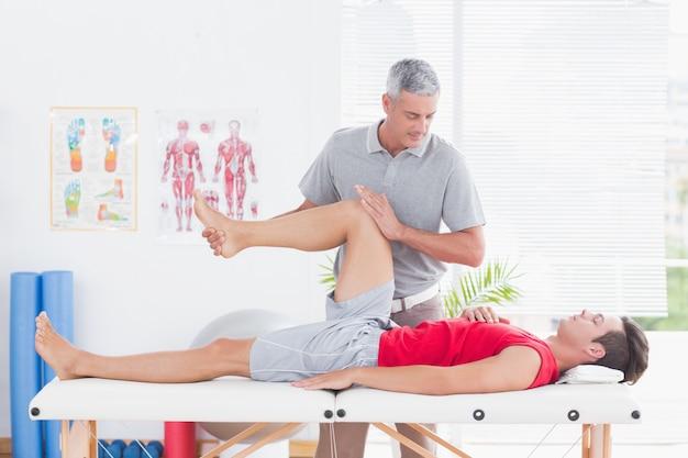 Physiotherapeut, der beinmassage zu seinem patienten tut