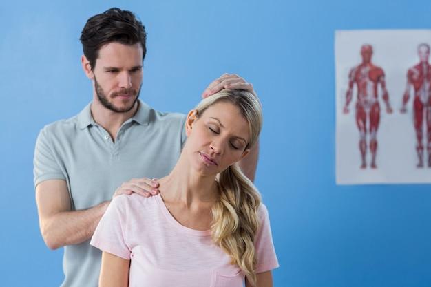 Physiotherapeut, der den hals einer patientin streckt