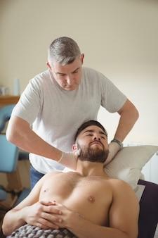 Physiotherapeut, der den hals eines patienten untersucht