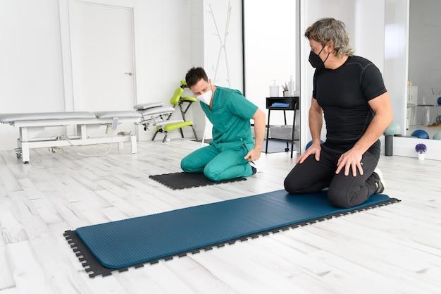 Physiotherapeut, der den mann bei der durchführung der übung auf der matte unterstützt