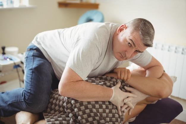 Physiotherapeut, der den rücken eines patienten untersucht