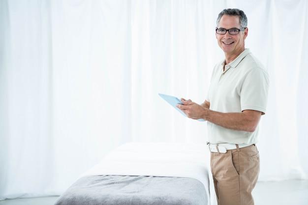 Physiotherapeut, der digitale tablette in seiner klinik verwendet