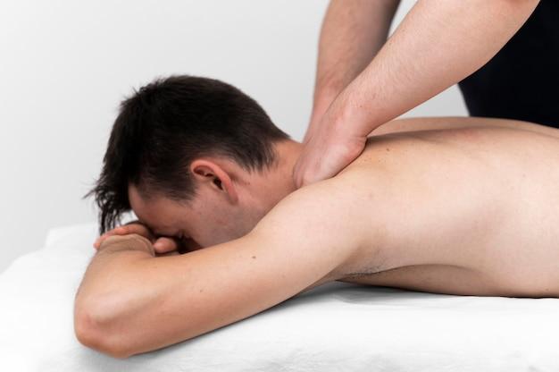 Physiotherapeut, der eine rückenmassage für männliche patienten durchführt