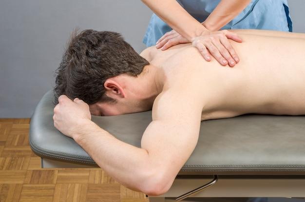 Physiotherapeut, der eine rückenmassage tut, um patienten zu bemannen. osteopathie.