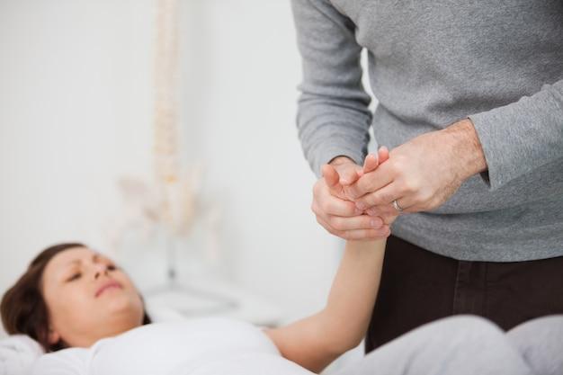 Physiotherapeut, der eine schmerzhafte hand massiert