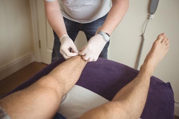 Physiotherapeut, der eine trockennadelung am bein eines patienten durchführt