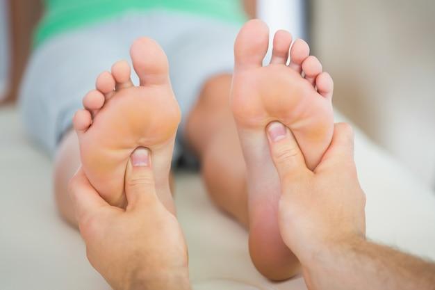 Physiotherapeut, der einem patienten eine fußmassage gibt