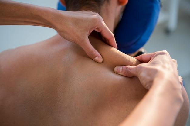 Physiotherapeut, der einem patienten eine rückenmassage gibt