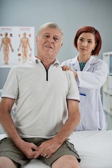 Physiotherapeut, der einen älteren patienten untersucht, massiert verschiedene triggerpunkte auf seinem rücken und fragt, ob es wehtut