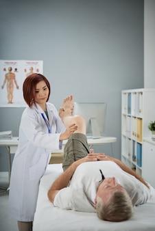 Physiotherapeut, der einen älteren patienten untersucht, um bewegungsstörungen zu diagnostizieren und einen behandlungsplan zu entwickeln, der dazu beiträgt, die behinderung zu reduzieren