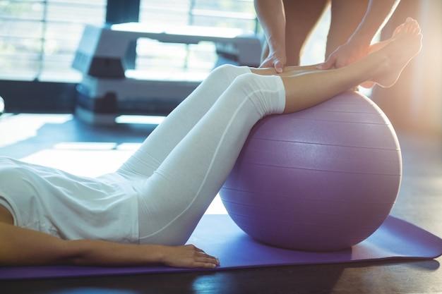 Physiotherapeut, der einen patienten mit gymnastikball unterstützt
