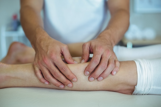 Physiotherapeut, der einer frau beinmassage gibt