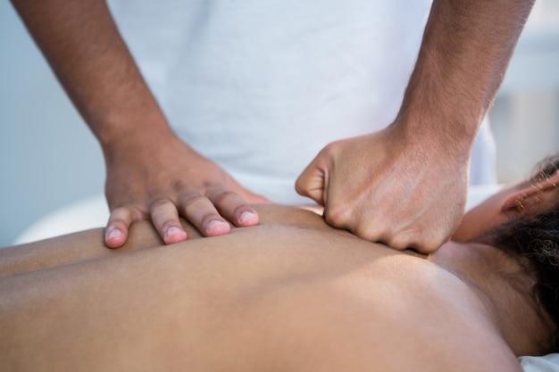 Physiotherapeut, der einer frau eine rückenmassage gibt
