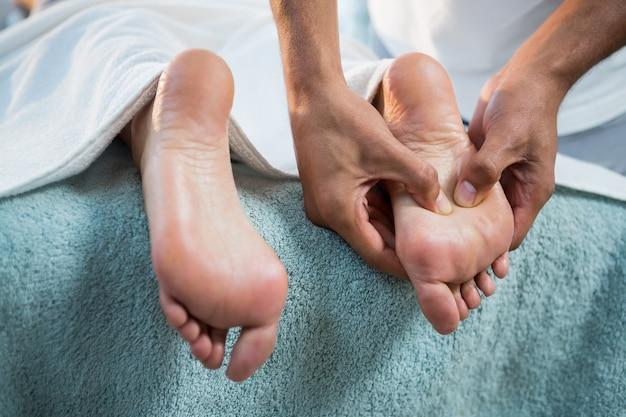 Physiotherapeut, der einer frau fußmassage gibt