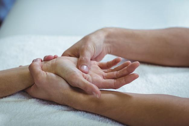Physiotherapeut, der einer frau handmassage gibt