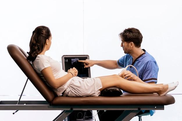 Physiotherapeut, der einer frau in der klinik knietherapie gibt. physikalisches behandlungskonzept