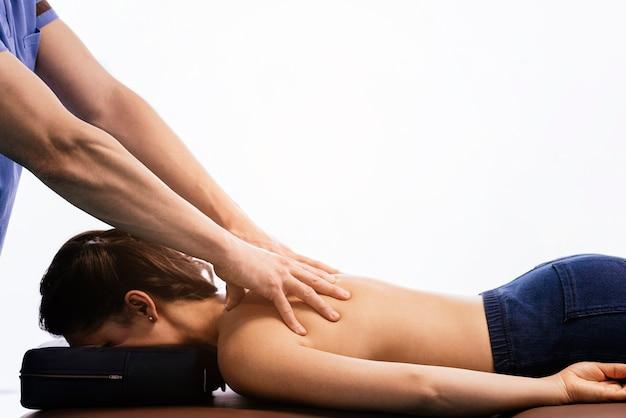 Physiotherapeut, der einer frau in der klinik rückenschlagtherapie gibt. physikalisches behandlungskonzept