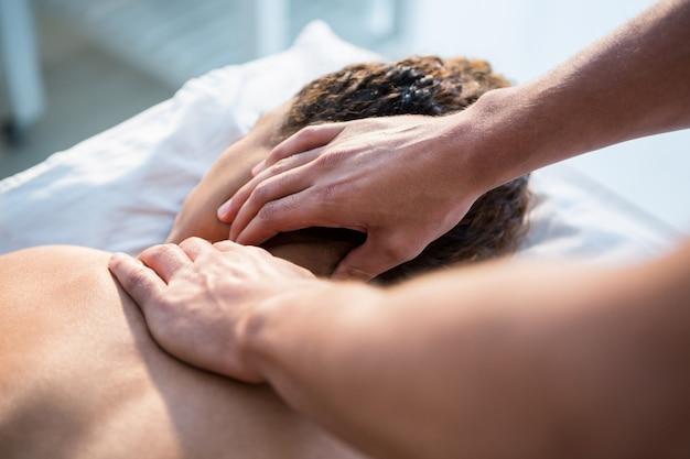 Physiotherapeut, der einer frau nackenmassage gibt