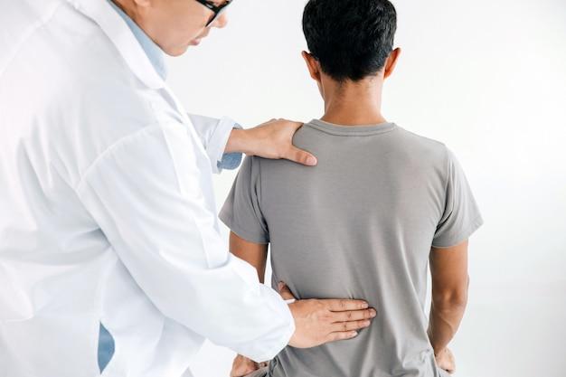 Physiotherapeut, der heilbehandlung auf dem rücken des mannes tut. rückenschmerzen patient