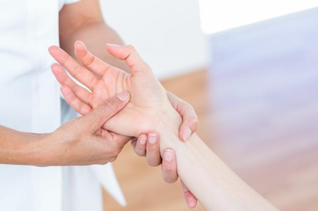 Physiotherapeut, der ihre patientenhand massiert