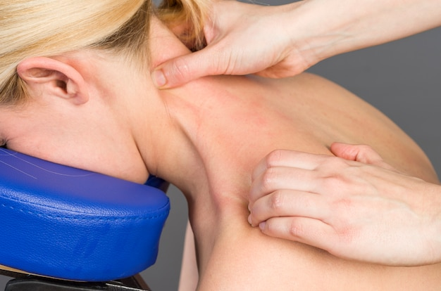 Physiotherapeut, der ihren patienten zurück überprüft und dekontraktierende massage tut.