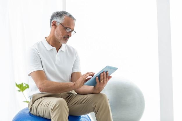 Physiotherapeut, der im übungsball sitzt und zu hause digitale tablette verwendet